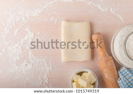 Puff pastry dough. Homemade folded raw puff pastry on a table. Making puff pastry. Dough's roll with a rolling pin, flour,  butter and cloth with copy space. #1015749319