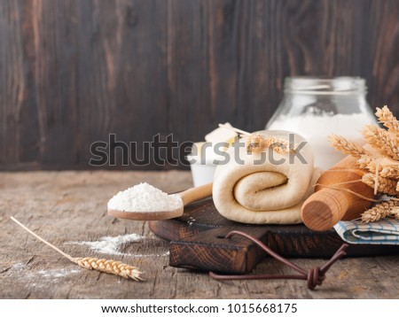Puff pastry dough. Homemade folded raw puff pastry on a wooden cutting board on a rustic wooden surface (table). Making puff pastry. Dough's rolls with a rolling pin, flour, butter, wheat spikelets. #1015668175