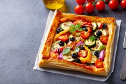 Puff pastry pizza with grilled vegetables. Grey background. Close up.