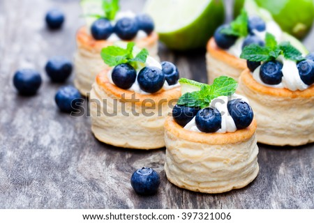 puff  pastry stuffed with soft cream cheese and blueberry with lime on rustic table  #397321006