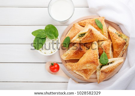 Puff pastry triangles filled with feta cheese and spinach on wooden table.top view #1028582329