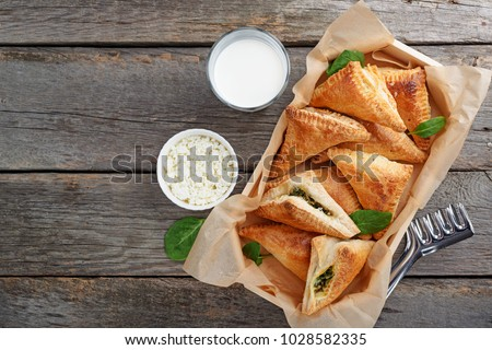 Puff pastry triangles filled with feta cheese and spinach on wooden table.top view #1028582335