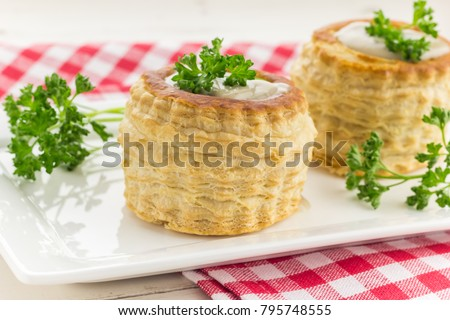 Puff pastry vol-au-vents filled with mushroom ragout, topped with fresh parsley #795748555