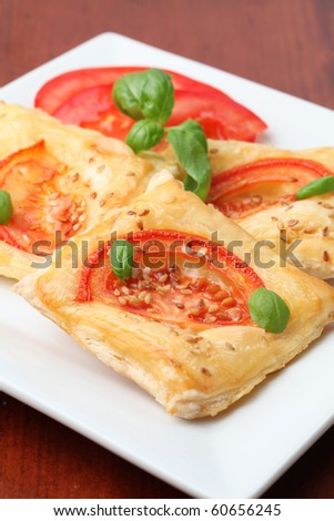 Puff pastry with cheese and tomatoes seasoned with sesame seeds