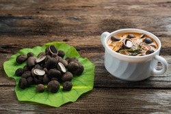 Puffball red curry in white soup bowl with fresh organic puffball mushrooms on lotus leaf on wooden table background. Most popular and expensive wild mushroom only in Northern Thailand.
