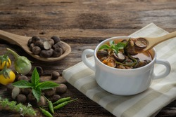 Puffball red curry in white soup bowl with fresh organic puffball mushrooms on wood spoon and on wooden table with green basil leave. Most popular and expensive wild mushroom only in Northern Thailand