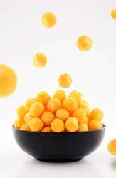puffed ball cheese corn chips in black bowl and sprinkled isolated on white background