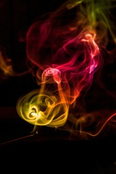 Puffs of smoke from a candle against a dark background