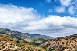 Puffy white clouds cover sky and mountain tops in Southern California