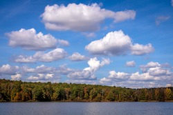 Puffy white clouds over lake with autumn leaf color
