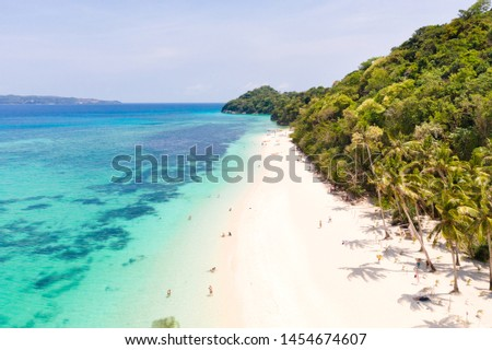 Photo of  Puka Shell Beach. Wide tropical beach with white sand. Beautiful white beach and azure water on Boracay island, Philippines, top view. Tourists relax on the beach.