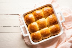 Pull apart bread buns in a white ceramic tray on a wooden table above view. Home-baked bread buns made with sourdough and white flour. Golden crust bread freshly baked.
