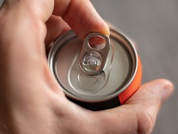 Pull the tab of an aluminum beverage can of an energy drink with male hands on neutral background