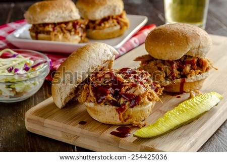 Pulled pork barbeque sliders sitting on wooden cutting board with dill pickle and additional sliders in background with beer