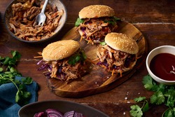 Pulled pork burgers with pickled and fresh vegetables and coriander on brown wooden background