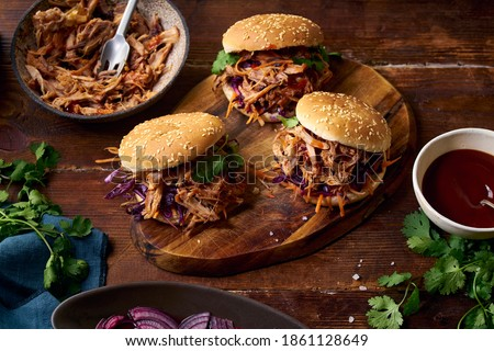 Photo of  Pulled pork burgers with pickled and fresh vegetables and coriander on brown wooden background