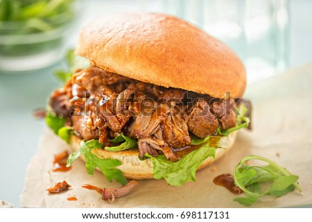 Pulled pork sweet bun with mixed lettuce leaves