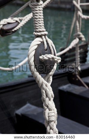 Pulley block on an old wooden sail boat with ropes
