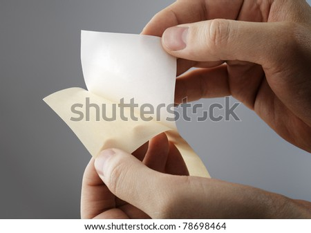Pulling away a sticker from its backing paper aka. release paper.