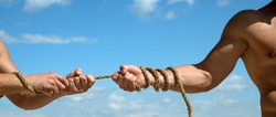 Pulling rope. Male hands pull opposite ends of rope. Tug war is a sport. Test of muscular strength. Opposite teams. Athletic contest. Sport competition. Physical strength and muscular power.