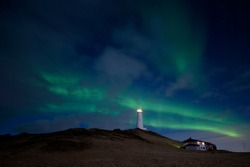 Pulsating northern light waves on a cloudy night sky with a lighthouse and light keeper house on a hill