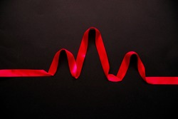 Pulse of red satin ribbon on a black background. The topic of health. Abstract background.