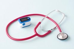 Pulse Oximeter, finger digital device to measure person's oxygen saturation with a stethoscope. Reduced oxygenation is an emergency sign of pneumonia caused by flu or novel coronavirus.