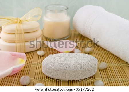 Pumice stone, white bath towel, bars of soap, scented candle./Clean Feet