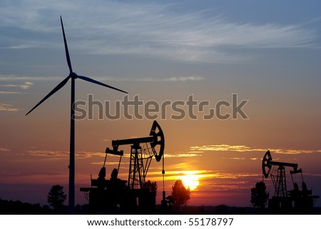 pump and wind turbine on sunset background