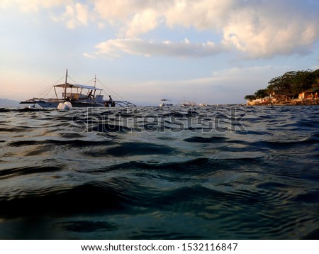 Pump boats on the sea at sunset in Moalboal, Cebu, Phillipines #1532116847