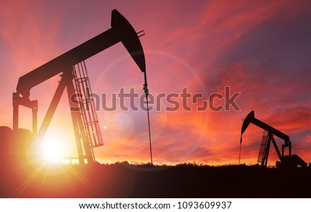 Pump jack silhouette against a sunset sky with deliberate lens flare and copy space. These jacks can extract between 5 to 40 litres of crude oil and water emulsion at each stroke.