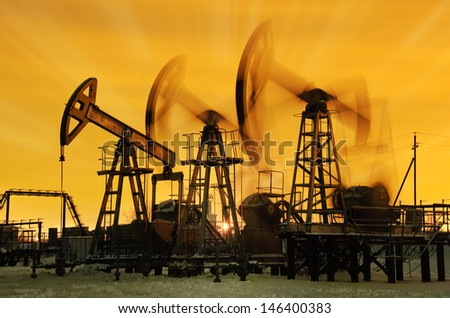 Pump jacks  at sunset sky background. - stock photo