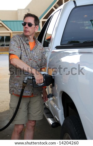 Pumping fuel into a gas guzzling pickup truck.