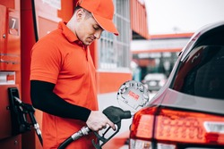 Pumping gas at gas station. Close up of a hand holding fuel nozzle.Refuel cars at the fuel pump. The driver hands, refuel and pump the car's gasoline with fuel at the petrol station.