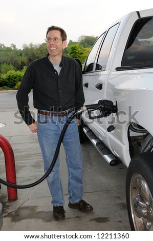 Pumping Gas into a gas guzzling truck.  Why is this man happy? - stock photo