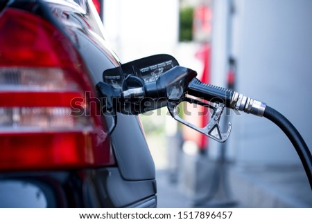 Pumping gasoline fuel in black car at gas station , Gas pump nozzle.