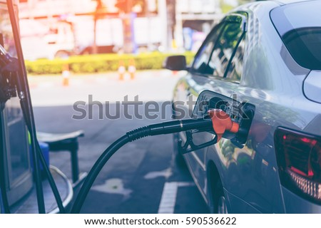 Pumping gasoline fuel in car at gas station