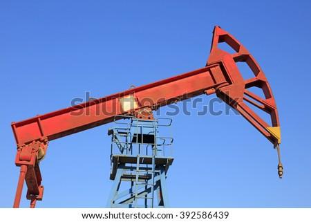 pumping unit walking beam under blue sky in oilfield #392586439