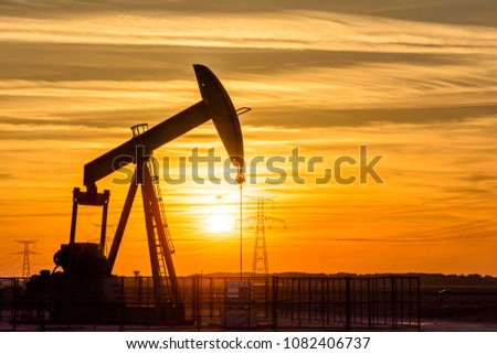 Pumpjack and transmission towers at sunset symbolizing energy transition. A pump jack pumping oil out of a well with silhouettes of electricity pylons and power line against a red sky. Foto stock ©