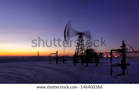 Pumpjack on the sunset sky background. Long exposure. Panorama.