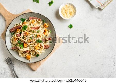 Pumpkin and Bacon Pasta with grated parmesan cheese. Homemade spaghetti pumpkin pasta on white, copy space. Seasonal autumn food.  Pumpkin Carbonara.