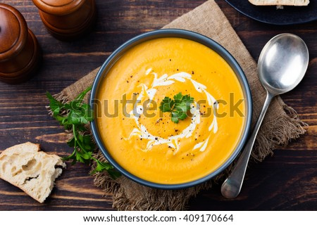 Pumpkin and carrot soup, tadka with cream and parsley on dark wooden background. Top view.