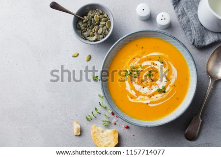 Pumpkin and carrot soup with cream on grey stone background. Copy space. Top view. Foto d'archivio ©