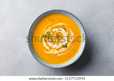 Pumpkin and carrot soup with cream on grey stone background. Top view.