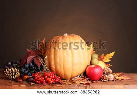 pumpkin, apples,berries and leaves on wooden table on brown background