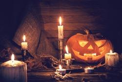 Pumpkin around burning candles