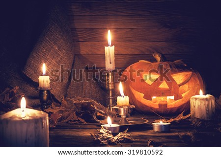 Pumpkin around burning candles