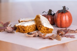 Pumpkin bars topped with cream cheese frosting surrounded with leaves, acorns, pumpkins and fall decor.