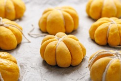 Pumpkin bread rolls prepared for baking on white parchment paper close up view