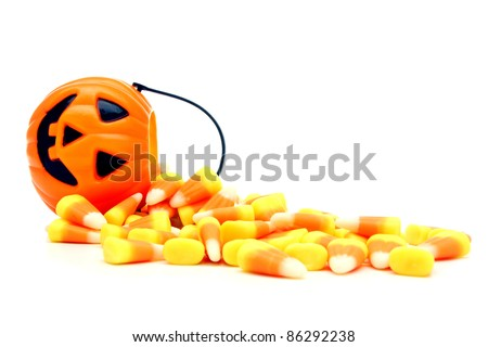 Pumpkin candy holder with spilling Halloween candy corn over white